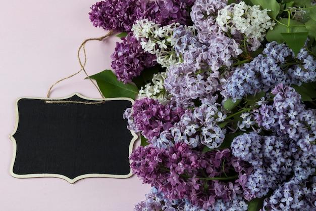 ピンク色の背景に色とりどりのライラックの花束と木製の碑文ボード