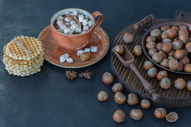ヘーゼルナッツ、ワッフル、マシュマロのクローズアップとホットチョコレートのカップ