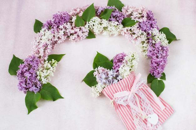 ライラックのアーチとバッグの中のライラックの花束