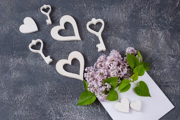 На сером фоне конверт с розовой сиренью, белыми сердечками и ключами
