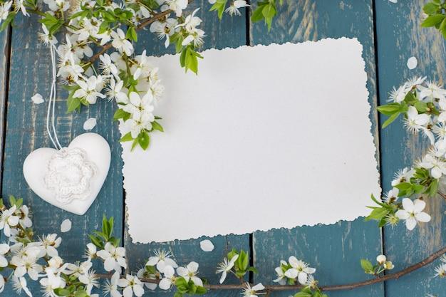 Цветущая ветка яблони, сердце и пустой лист бумаги