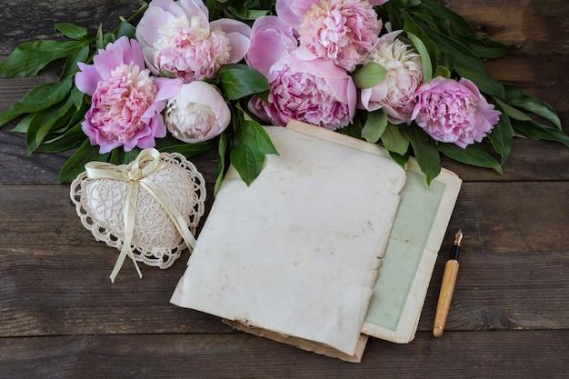 На деревянном столе букет розовых пионов, ручка, листы старой бумаги и сердце