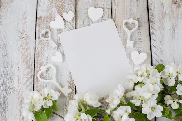 Яблоневый цвет, лист бумаги и ключи от сердца на белом фоне деревянные