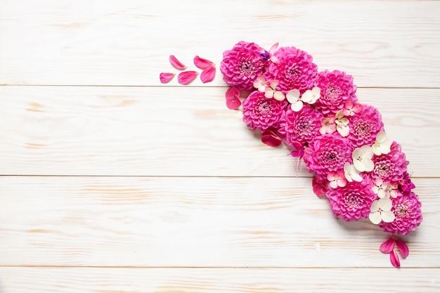 白い木製の背景にピンクのダリアと秋の花柄。