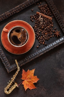 Миниатюрная копия саксофона, кофе, кофейные зерна и яркие осенние листья