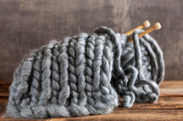 Вязание, толстые серые нити на деревянных спицах, клубок и холст, текстура,