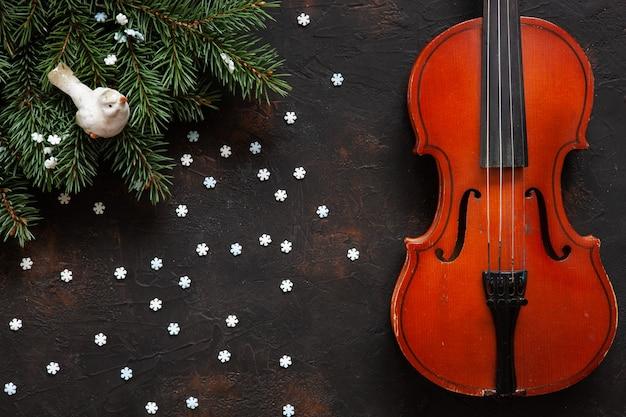 クリスマスの装飾が施された古いバイオリンとモミの木の枝。