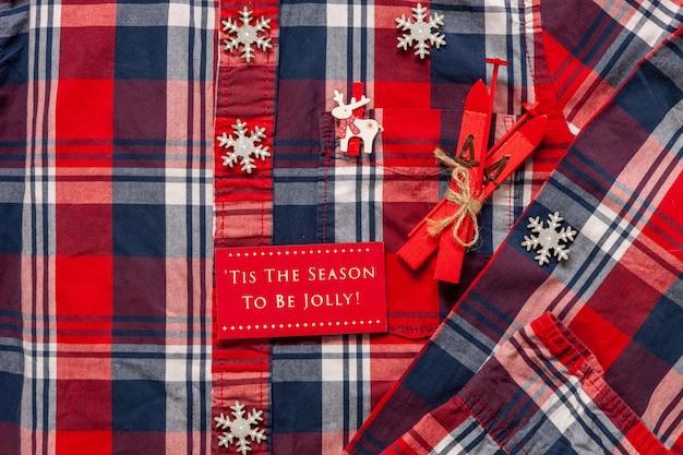 Рождественский лыжный декор на фоне мужской рубашки в яркой клетке.