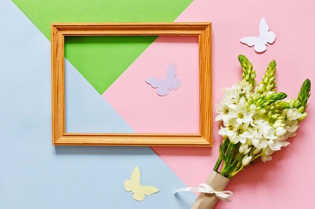 白い春の花とパステルカラーのキャンディー色の背景に蝶のシルエット。