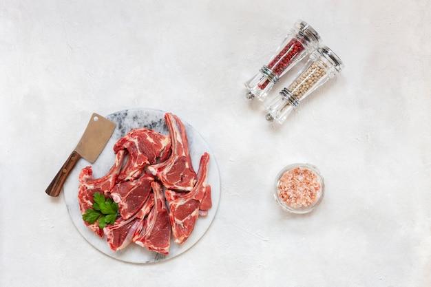 生の新鮮なラム肉リブと白い表面の調味料