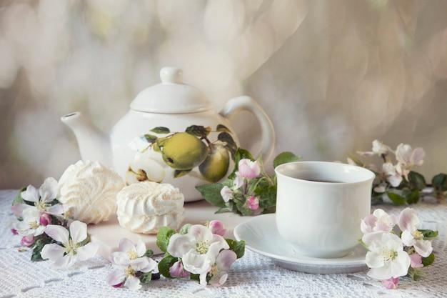一杯の紅茶とマシュマロの開花のリンゴの枝
