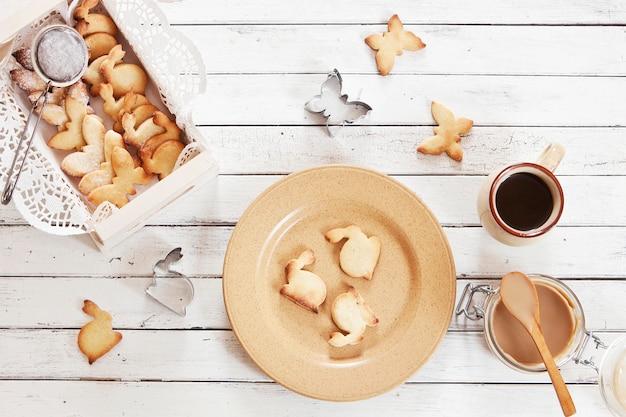 皿の上のかわいい蝶とウサギのクッキーのクローズアップ