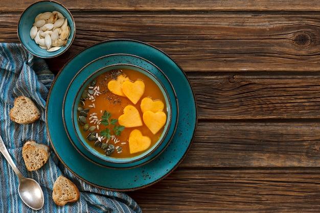 新鮮な自家製カボチャのクリームスープの種とハート型トーストプレート