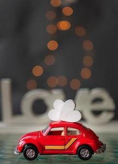 小さなおもちゃの赤い車の屋根の上の心