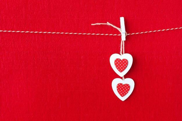 Закройте белые деревянные сердечные символы на фоне красной бумаги