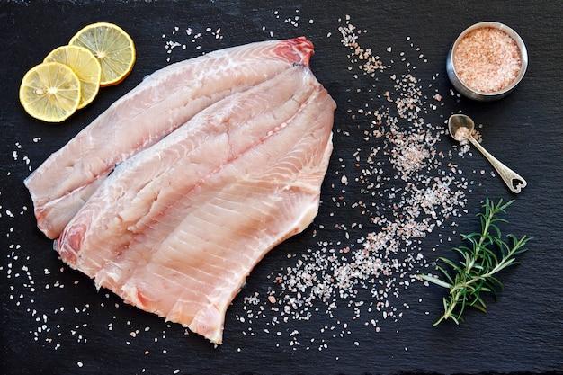 海の塩と黒のコンクリートテーブルの背景にレモンの新鮮な生の魚の切り身のクローズアップ写真。