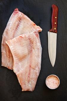 海の塩と黒のコンクリートテーブルの背景にナイフと新鮮な生の魚の切り身のクローズアップ写真