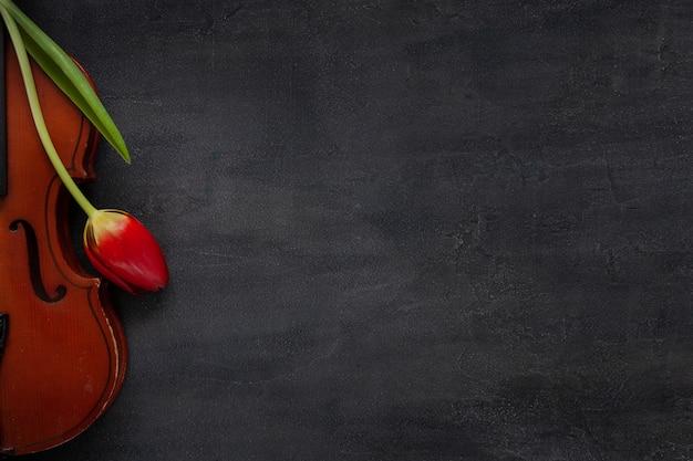 古いバイオリンと赤いチューリップの花。トップビュー、暗いコンクリートの背景にクローズアップ