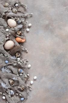Пасхальное украшение - натуральные яйца и верба. вид сверху, крупный план, плоская планировка на светлом бетонном фоне