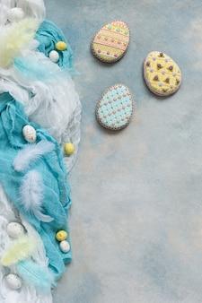 Пасхальное украшение - яйца из пряников и сладких конфет. вид сверху, крупный план, плоская планировка на светлом бетонном фоне
