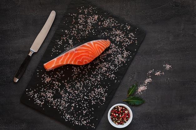 海の塩、紙と新鮮な生のサケの魚の切り身のクローズアップ写真