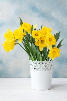 空色の背景上の花瓶に新鮮な黄色の水仙の花束