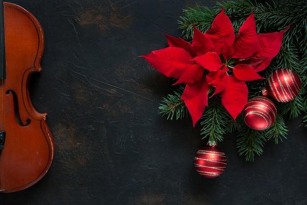 クリスマスの装飾とポインセチアの古いバイオリンとモミの木の枝