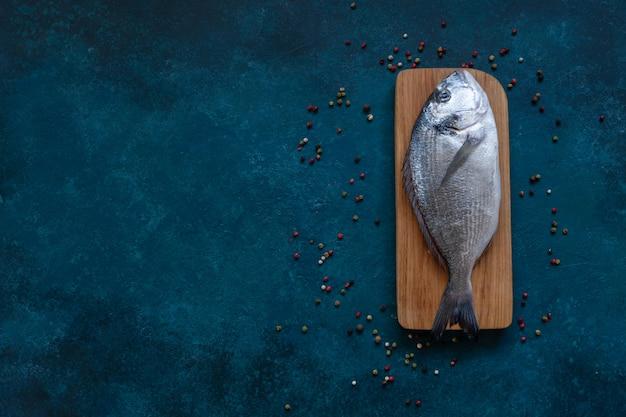 青いテーブルの上の木製のまな板の上の新鮮なドラド魚