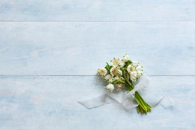 水色の木製の背景にスノードロップの花束