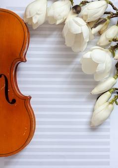 古いバイオリンとメモ用紙に開花のマグノリア。上面図、クローズアップ。
