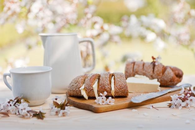 冷たい牛乳瓶とガラスで木の板にバター焼きたての自家製パンのクローズアップ