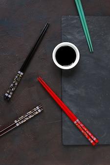 Разноцветные палочки для еды и соевый соус на черном каменном фоне