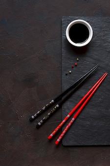 Палочки для еды и миску с соевым соусом на черном фоне камня