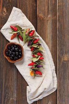 色とりどりの唐辛子、月桂樹の葉と木製のボウルにブラックオリーブの葉。