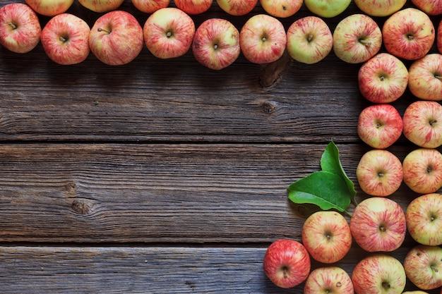 Свежие красные яблоки на деревянных фоне в винтажном стиле.