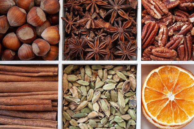 シナモンの樹皮、ヘーゼルナッツ、アニス、ピーカンナッツ、ドライオレンジとカルダモンのスライスの写真を閉じます。