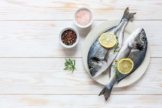 スパイス、オリーブオイル、ニンニク、白いテーブルに白い皿に調味料と新鮮なドラド魚。