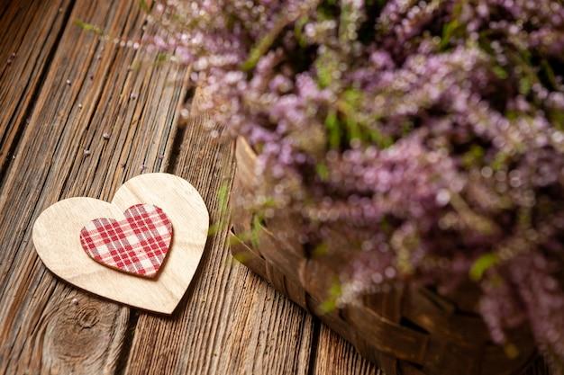 バスケットとハートのシンボルに咲く森ヘザーの美しい新鮮な花束