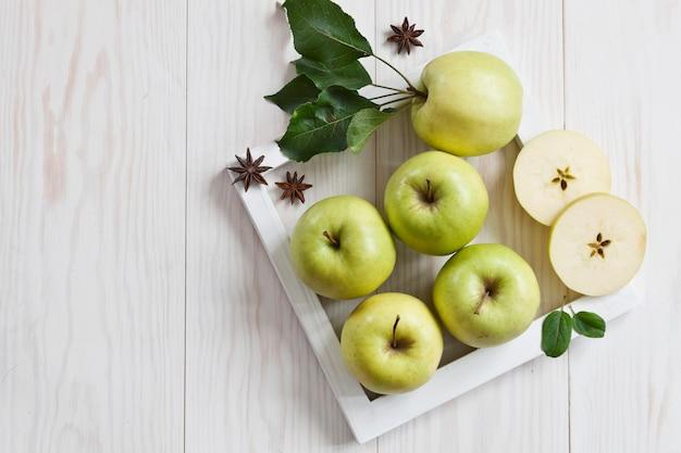 白い木製の背景に白いフレームに緑のリンゴ。