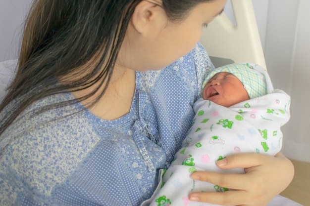 母親は、出産後すぐにベッドで生まれたばかりの赤ちゃんを見ます。妊娠中の女性、新生児、赤ちゃん、妊娠のコンセプト写真。