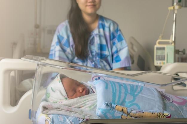 Мама смотрит на своего новорожденного ребенка в постели сразу после родов. концепция фото беременной женщины, новорожденного, ребенка, беременность.
