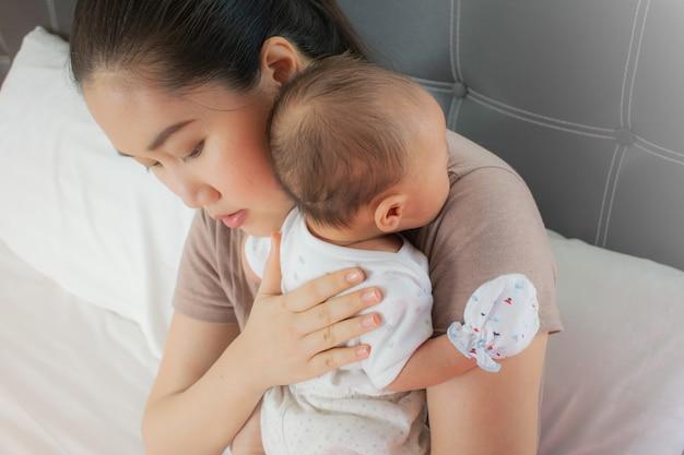 美しい母親は彼女のかわいい赤ちゃんを保持しています。幼児が肩に横になってげっぷをする、