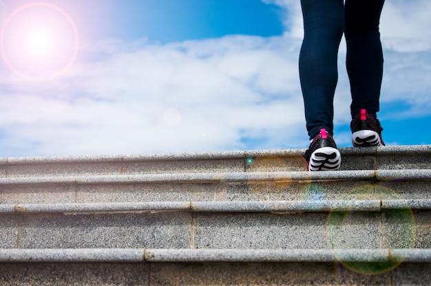 女性は青い空を背景に階段のてっぺんまで歩いています。