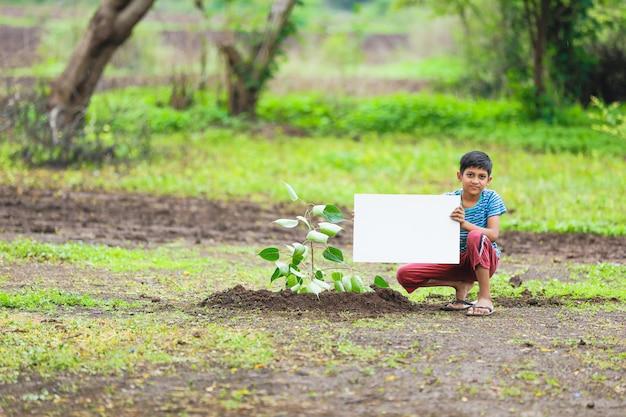 空のポスターを保持しているインドの子供