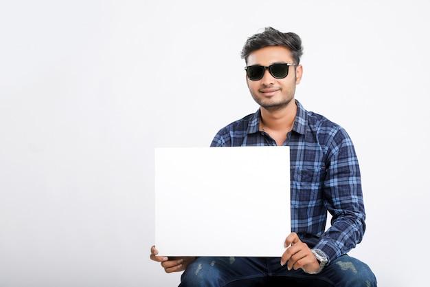 Молодой индийский мужчина держит плакат