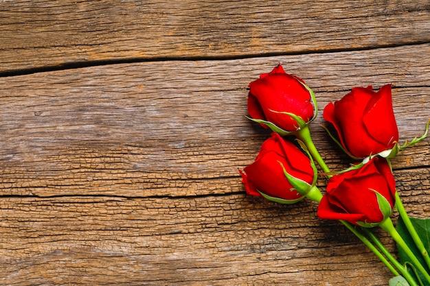 木製の背景にコピースペースを持つ赤いバラの花。バレンタインの日の概念