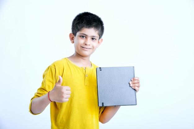 ノートブックと若いインドのかわいい男の子