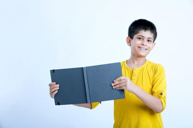 ノートを保持している若いインドの少年