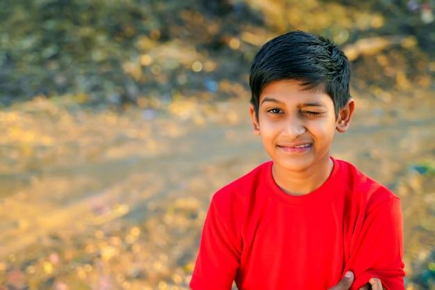 Портрет красивого подмигивающего маленького мальчика в красной футболке