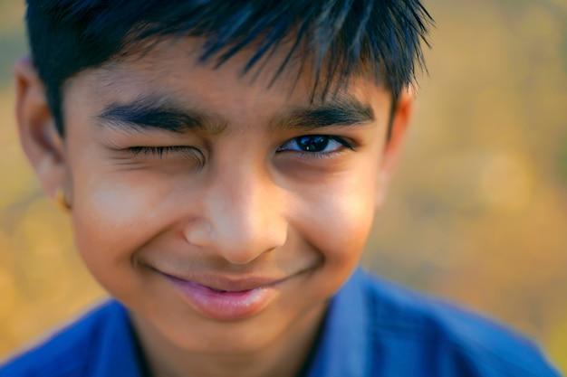 Портрет красивой индийской подмигивая маленького мальчика
